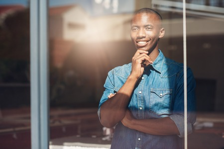 Handsome young African man standing in his design studio looking optimistically out of his window and thinking about his future plans, with shining sunlight reflecting on the glass