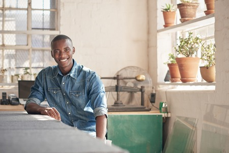 framer: Young man of African descent sitting at his designer work bench and smiling comfortably at the camera, with soft light through the windows of his workshop Stock Photo