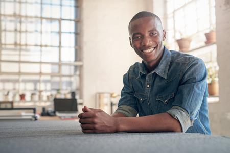 Laag hoekportret van een knappe jonge Afrikaanse kleine bedrijfseigenaarzitting bij een het werk bank in zijn prachtig aangestoken workshop, die vol vertrouwen bij de camera glimlachen