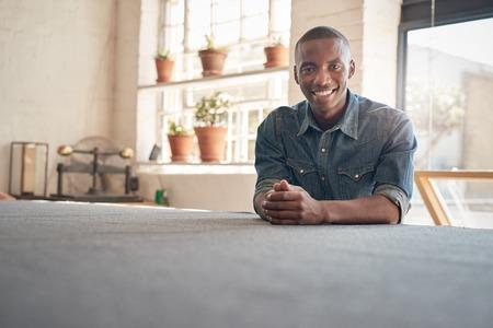 彼のワーク ショップ スタジオで座って、カメラで笑顔のアフリカ降下の自信を持って若い経営者の肖像 写真素材