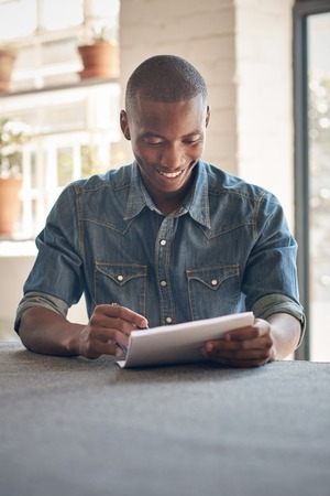 african descent: Handsome young man of African descent sitting in a beautifully lit space smiling while filling in some paperwork