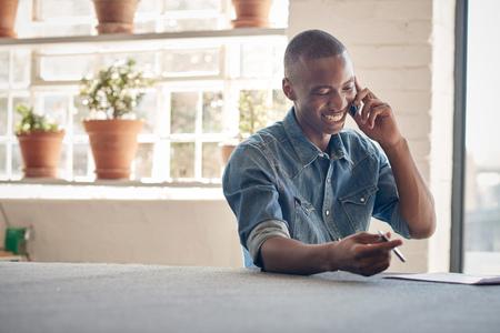 Jonge Afrikaanse man met een mooie glimlach, gelukkig praten op zijn mobiele telefoon tijdens de vergadering in een prachtig verlichte ontwerper studio Stockfoto - 57155986
