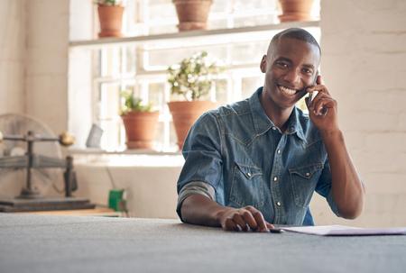 Potrait van een knappe jonge man van Afrikaanse afkomst zit in zijn prachtig verlicht design studio, die op zijn mobiele telefoon over zijn kleine bedrijven, en lachen naar de camera