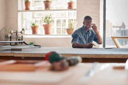 ハンサムな若いアフリカ デザイナーに座っている彼のワーク ショップ、彼の起業家のビジネスに関連する作業を議論する彼の携帯電話で話しながら