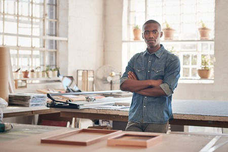 framer: Young man of African descent standing proudly with his arms folded in the workshop where he runs his small business from, looking at the camera seriously Stock Photo