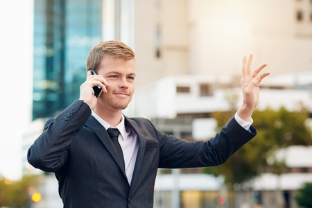 hailing: Businessman talking on the phone hailing a taxi while standing in the city Stock Photo