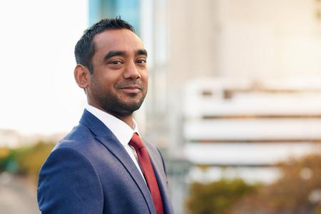 persona feliz: Retrato de un hombre de negocios sonriente con la ciudad en el fondo