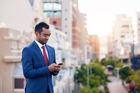 Businessman sending a text message on a cellphone while walking in the city