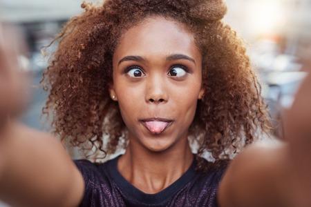 sacar la lengua: Retrato de una mujer joven que hace una cara tonta a cabo mientras se hace una autofoto en la ciudad