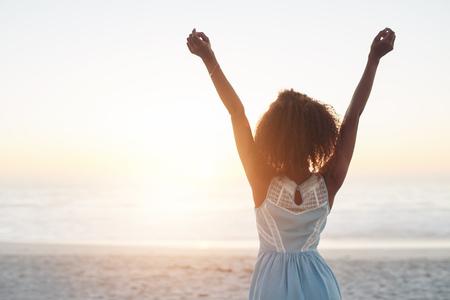 mujer mirando el horizonte: Hermosa mujer joven de pie en una playa con los brazos levantados en el aire