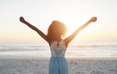 그녀의 팔을 공중에 제기와 함께 해변에 서있는 아름 다운 젊은 여자 스톡 콘텐츠