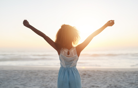 soledad: Hermosa mujer joven de pie en una playa con los brazos levantados en el aire