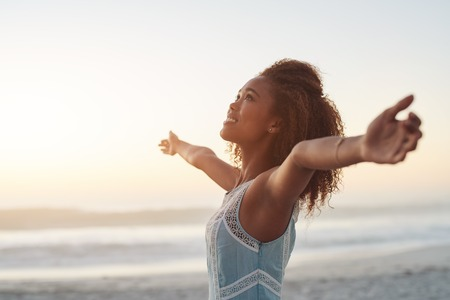 Beautiful young woman standing on a beach with her arms raised in the air