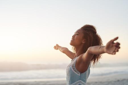 Hermosa mujer joven de pie en una playa con los brazos levantados en el aire Foto de archivo - 60118889