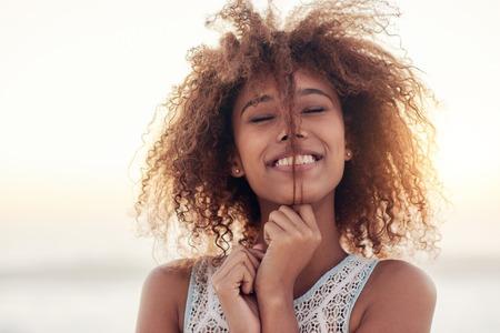 夕暮れのビーチに立っている美しい若い女性