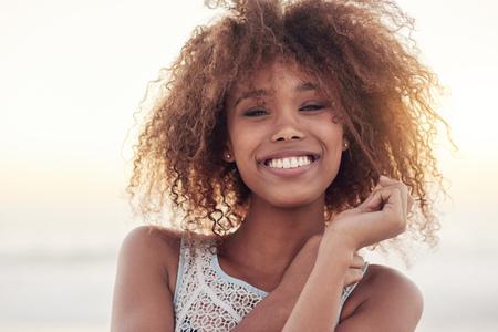 Porträt einer schönen jungen Frau auf einem Strand bei Sonnenuntergang Standard-Bild - 60096650