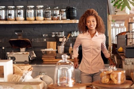 african business: Portrait of an attractive young woman standing behing the counter of a cafe Stock Photo