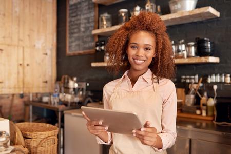 カフェで働いている間デジタル タブレットを使用して魅力的な若い女性の肖像画 写真素材