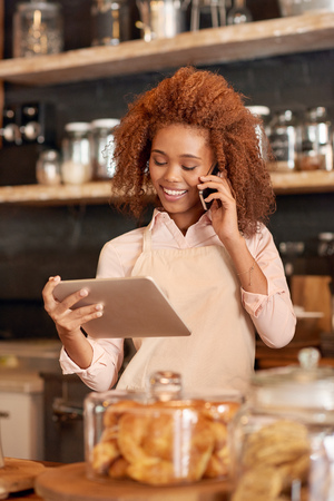 ethnic woman: Attractive young woman using a digital tablet and talking on the phone while working in a cafe