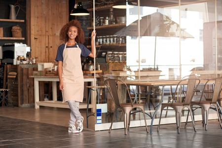 Portrait of an attractive young woman standing in front of a cafe Stock Photo