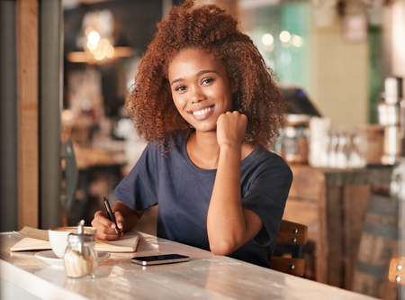 Portrait of an attractive young woman writing in a book while sitting in a cafe