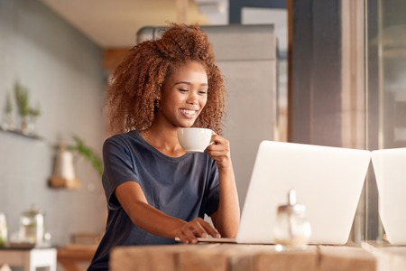 Attractive young woman working on a laptop and drinking coffee while sitting in a cafe