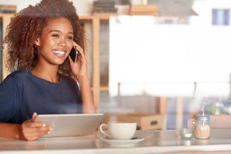Aantrekkelijke jonge vrouw gebruikend een digitale tablet en sprekend op de telefoon terwijl het zitten in een koffie