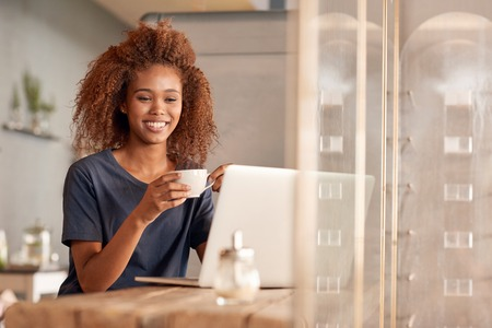ethnic woman: Attractive young woman working on a laptop and drinking coffee while sitting in a cafe