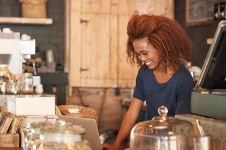 belle brune: Attractive jeune femme utilisant un ordinateur portable tout en travaillant dans un café