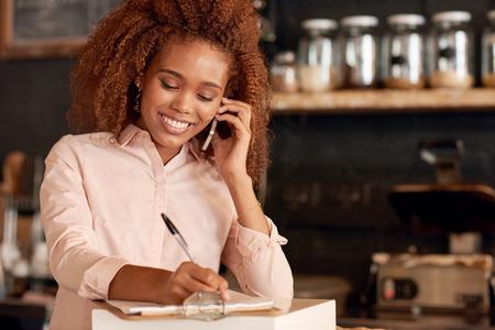 매력적인 젊은여자가 카페에서 작업하는 동안 전화로 얘기