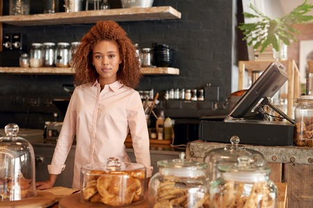 Portrait of an attractive young woman standing behing the counter of a cafe Stock Photo