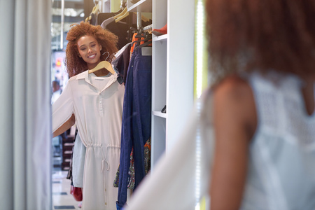 reflection mirror: Attractive young woman with curly hair smiling and  trying on clothes in a mirror while standing in a clothing store