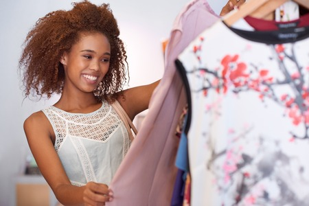 clothing shop: Attractive young woman with curly hair  browsing through clothes hanging on racks while standing in a clothing shop