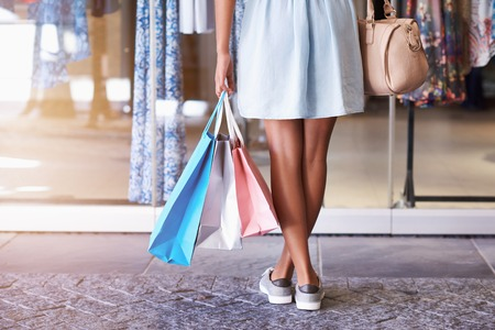 womans clothing: Closeup of a young womans legs standing in front of a clothing store holding many shoppping bags and her handbag, standing in front of a store window Stock Photo