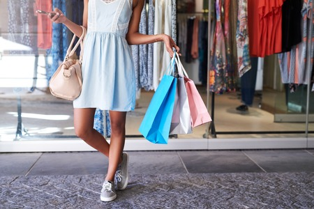 Closeup of a young womans legs standing in front of a clothing store holding many shoppping bags and her cellphone, standing in front of a store window