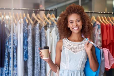 cabello rizado: Retrato de una mujer joven y atractiva con el pelo rizado sonriente y beber un café mientras disfruta de un día de compras en un centro comercial