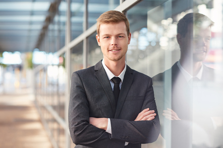 Portrait of a confident and successful businessman standing with his arms crossed outside leaning against the glass windows of a modern office building Foto de archivo