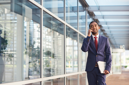 Confident and successful businessman talking on a cellphone while walking in front of the glass windows of a modern office building