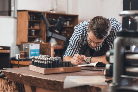 jewelries: Jeweler leaning on a bench sketching out new jewelry designs in a notebook while working in his shop