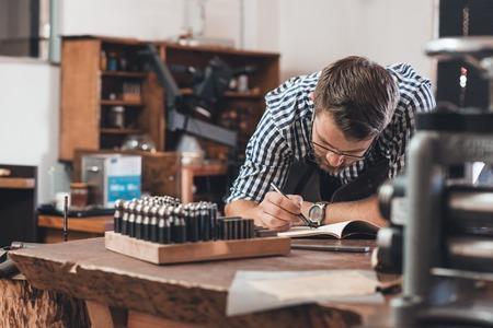 Joyero apoya en un banco esbozar nuevos diseños de joyas en un bloc de notas mientras se trabaja en su taller