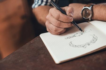 Close-up van een juwelier leunend op een bankje het schetsen van nieuwe sieraden ontwerpen in een notebook tijdens het werken in zijn winkel