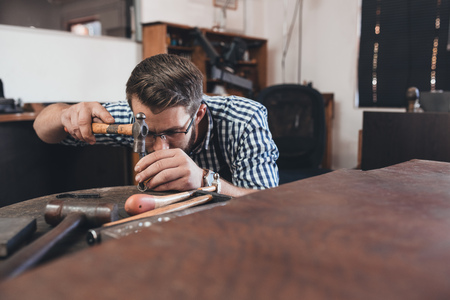 designer at work: Focused jeweler in an apron using a hammer to shape a new ring while working at a bench in his workshop Stock Photo
