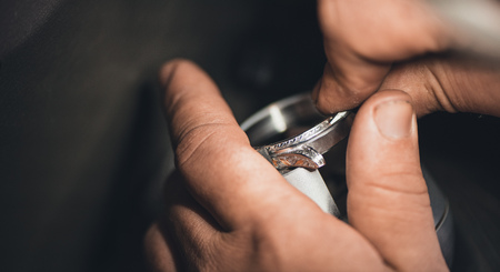 designer at work: Closeup of a jeweler using tools to shape a silver ring while working at a bench in his workshop