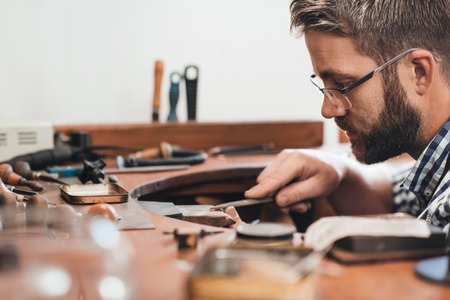 Jeweler sitting at a bench in his workshop using a file to shape and smooth out a silver ring Stock Photo