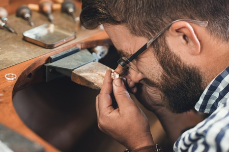Closeup of a jeweler using a loupe to examine a gem he is working with while sitting at a bench in his workshop Zdjęcie Seryjne
