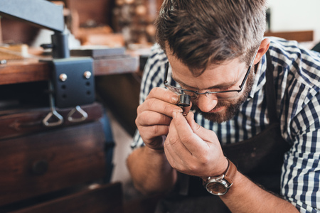 crafting: Closeup of a jeweler using a loupe to examine a gem he is working with while sitting at a bench in his workshop Stock Photo
