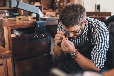 Juwelier mit einer Lupe ein Juwel zu prüfen, arbeitet er mit, während in seiner Werkstatt auf einer Bank sitzen Standard-Bild - 65196527