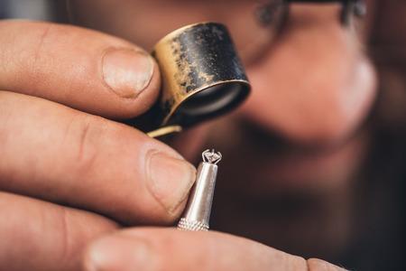그는 그의 워크샵에서 벤치에 앉아있는 동안 다이아몬드를 검사하는 부분 확대를 사용하여 보석상의 근접 촬영