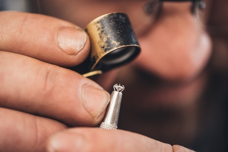 Closeup of a jeweler using a loupe to examine a diamond he is working with while sitting at a bench in his workshop
