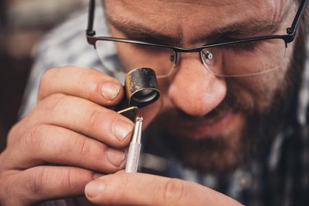 Gros plan d'un bijoutier en utilisant une loupe pour examiner un diamant, il travaille avec alors qu'il était assis sur un banc dans son atelier